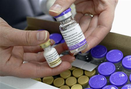 A nurse holds a bottle of the Pandemrix H1N1 flu vaccine (R) and a bottle of the vaccine's adjuvant (L) at a health centre in Burgos in this November 16, 2009 file photo. REUTERS/Felix Ordonez/Files