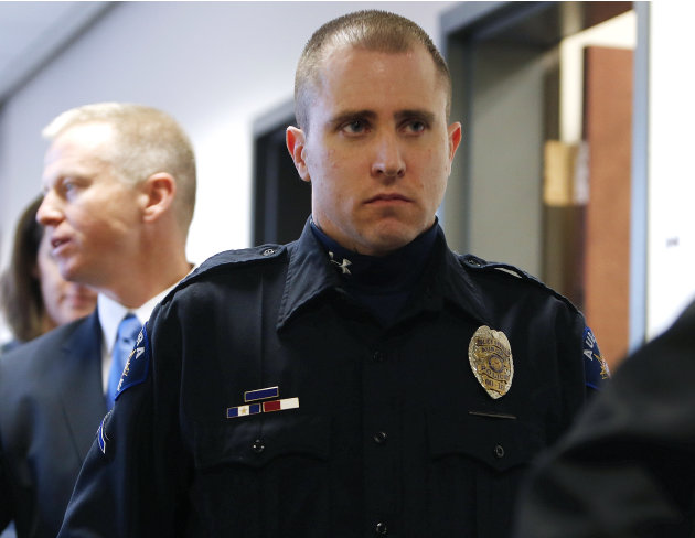 Aurora Police Officer Justin Grizzle leaves court after testifying at a preliminary hearing for James Holmes at the courthouse in Centennial, Colo., on Monday, Jan. 7, 2013. Investigators say Holmes o