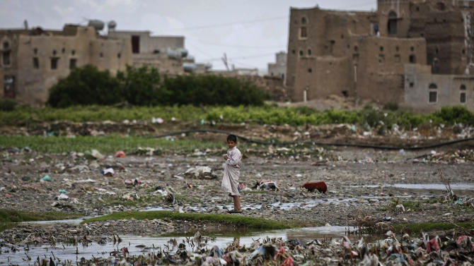 A Yemeni boy stands in the middle of garbage at a slum area on the outskirts of Sanaa, Yemen, Monday, April 22, 2013. Hundreds of countries globally, mark International Earth Day on April 22, to help raise ecological awareness and support environmental protection. (AP Photo/Hani Mohammed)