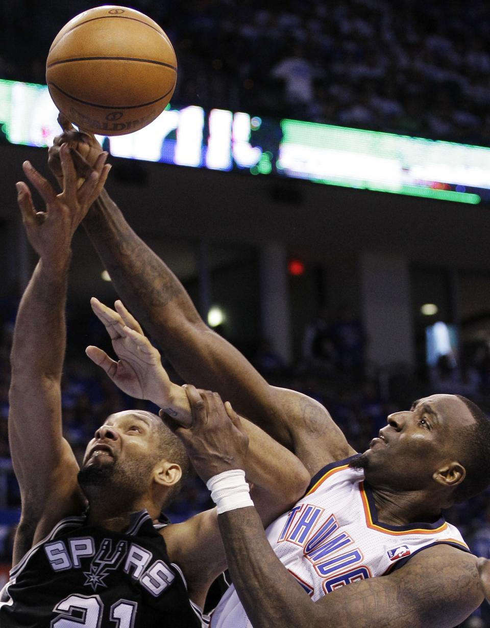 San Antonio Spurs center Tim Duncan (21) shoots as Oklahoma City Thunder center Kendrick Perkins defends during the first half of Game 4 in the NBA basketball playoffs Western Conference finals, Saturday, June 2, 2012, in Oklahoma City. (AP Photo/Eric Gay)