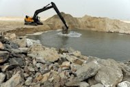 <p>A caterpillar digs reclaimed land from the sea on January 31, 2013, in Lagos, during the building of a three-and-a-half kilometre sea defence barrier that will shield Eko Atlantic from erosion.</p>