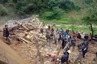 Rescuers search for victims after a landslide, triggered by sustained rains, buried a school and three farmhouses in Yiliang, southwest China's Yunnan province. The bodies of all 18 schoolchildren buried under a landslide in China have been recovered, officials said, as authorities defended returning them to school following recent deadly earthquakes