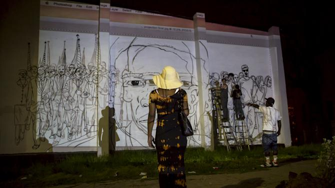 A woman stands in front of a mural being painted near the Gilmor Homes housing projects in Baltimore, Maryland