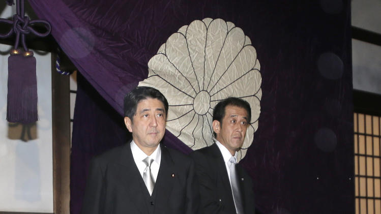 FILE - In this Oct. 17, 2012 file photo, Japan's main opposition Liberal Democratic Party President Shinzo Abe, left, leaves the Yasukuni Shrine after he paid homage to the war dead in Tokyo after he became the party leader. The LDP's victory in Japan's parliamentary election Sunday, Dec. 16, 2012 virtually ensures that Abe, who resigned as prime minister for health reasons in 2007 after just a year in office, will get a second chance to try to lead Japan out of its economic slump. (AP Photo/Shizuo Kambayashi, File)