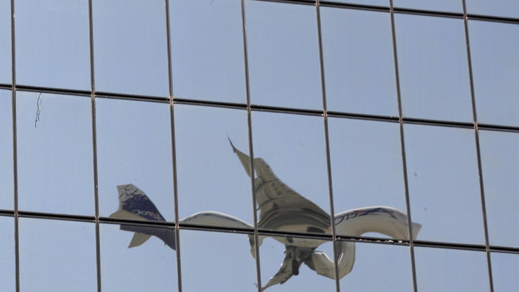 In this Jan. 15, 2013 photo, the windows of a building reflect the image of a plane approaching the Mariscal Sucre airport for landing in Quito, Ecuador. Mariscal Sucre airport sat amid cornfields when it was christened in 1960, and on Feb. 19, the airport will close and a new airport will be built. The runway will become a grassy esplanade, and a flurry of construction is anticipated nearby. The newly revised code will allow for buildings as high as 40 stories, up from the current four. (AP Photo/Dolores Ochoa)
