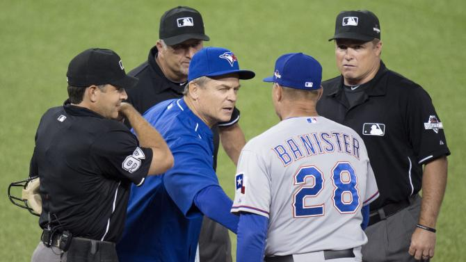 Toronto Blue Jays manager John Gibbons, center, shakes hands with Texas Rangers manager Jeff Banister before Game 1 of the American League Division Series in Toronto on Thursday, Oct. 8, 2015. (Darren Calabrese/The Canadian Press via AP) MANDATORY CREDIT