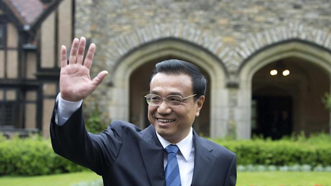 The Prime Minister of China , Li Keqiang waves after making a statement to the press outside of the Cecilienhof Castle  in Potsdam, Germany, Sunday May 26, 2013. The Chinese Premier is on his first official visit to Germany and will meet with Chancellor Merkel later today. (AP Photo/dpa,Marc Tirl)