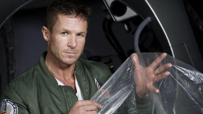 """In this Feb. 23, 2012 photo provided by Red Bull Stratos, pilot Felix Buamgartner of Austria shows a piece of the balloon material during the Red Bull Stratos egress training in Lancaster, Calif. It's described as a """"40-acre dry cleaner bag,"""" that, when first filled, will stretch 55 stories high. On Monday, this special ultra-thin helium balloon is scheduled to liftoff from Roswell, N.M., to carry """"Fearless Felix"""" Baumgartner 23 miles into the stratosphere for what he hopes will be a history-making, sound barrier-breaking skydive. (AP Photo/Red Bull Stratos, Joerg Mitter)"""
