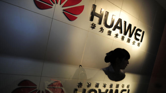 In this Monday, Oct. 8, 2012 photo, an employee works at a reception counter of a R&D center of Huawei Technologies Inc. in Wuhan, in central China's Hubei province. Eager to expand in the United States, China's biggest technology companies face American anxiety about security and rising Chinese competition.(AP Photo)  CHINA OUT