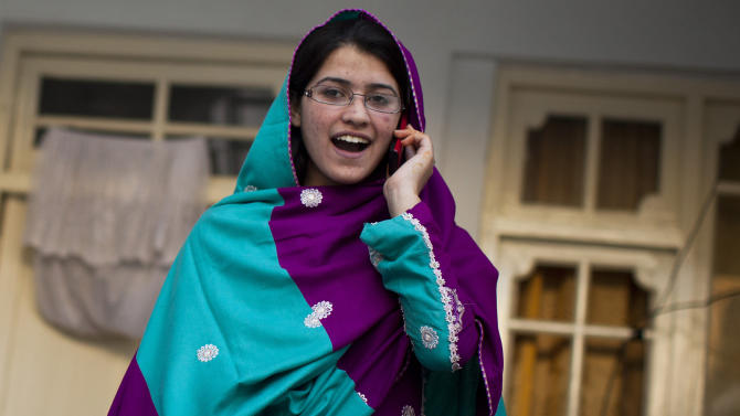 On this Wednesday, Nov. 14, 2012 photo, Pakistani girl Kainat Riaz, 16, answers a friends phone call at her home in Mingora, Swat Valley, Pakistan, after being wounded by the same Taliban gunman, who shot Malala Yousufzai and 13-year-old Shazia Ramazan, Oct 8, 2012 on their way coming back from school. Malala was shot for her outspoken insistence on girls education. Shazia and Kainat are to return to school this week for the first time since the shooting more than one month ago. ( AP Photo/Anja Niedringhaus)