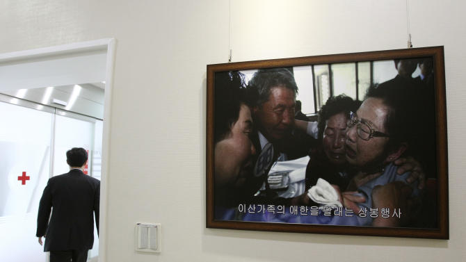 A picture showing the reunion of family members from North and South Korea is displayed at the Korean Red Cross headquarters in Seoul, South Korea, Tuesday, June 11, 2013. The two Koreas will hold their highest-level talks in years Wednesday in an effort to restore scrapped joint economic projects and ease animosity marked by recent threats of nuclear war. (AP Photo/Ahn Young-joon)