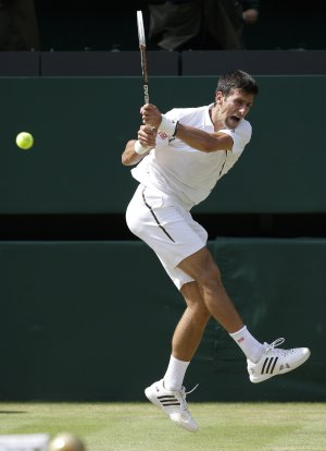Novak Djokovic of Serbia plays a return to Juan Martin…