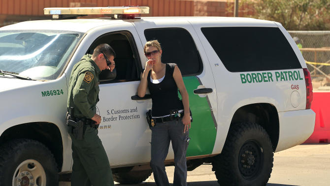 Hours after a U.S. Border Patrol agent was shot and killed, and another was shot and injured, Border Patrol agents stand in front of a Border Patrol vehicle in front of  the U.S. Customs and Border Protection Brian A. Terry Border Patrol Station Tuesday, Oct. 2, 2012, in Bisbee, Ariz. The agent and a colleague were on patrol in the desert near Naco, Ariz., about 100 miles from Tucson, when shooting broke out shortly before 2 a.m., the Border Patrol said. The second agent was shot in the ankle and buttocks, and was airlifted to a hospital. (AP Photo/Ross D. Franklin)