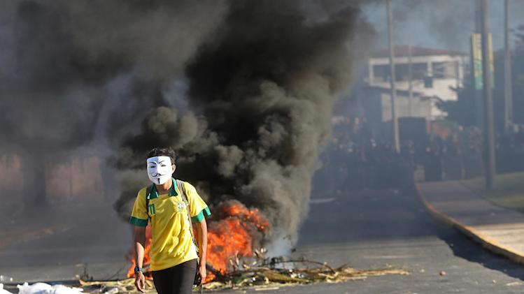 FILE - This June 19, 2013 photo, a masked protester walks away from a burning barricade near the Castelao stadium in Fortaleza, Brazil. Protesters cut off the main access road to the stadium where Brazil plays Mexico in the Confederations Cup soccer tournament later Wednesday. Beginning as protests against bus fare hikes, the demonstrations have quickly ballooned to include broad middle-class outrage over the failure of governments to provide basic services and ensure public safety. (AP Photo/Andre Penner, File)