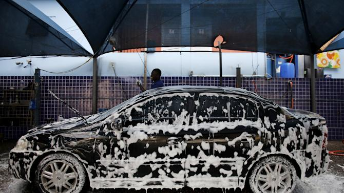Haitian immigrant washes a car at a car wash in Sao Paulo