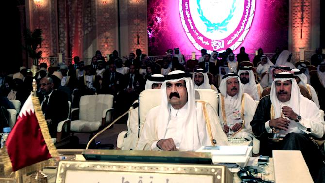 FILE - In this Tuesday, March 26, 2013 file photo, Emir of Qatar Sheik Hamad Bin Khalifa Al Thani, center, attends the opening session of the Arab League Summit in Doha. Qatar's emir moves to hand power over to his son, aiming to bring a youthful new face to rule in a tiny Gulf nation that has become one of the most powerful in the Middle East, aggressively spreading its influence through cash. (AP Photo/Ghiath Mohamad, File)