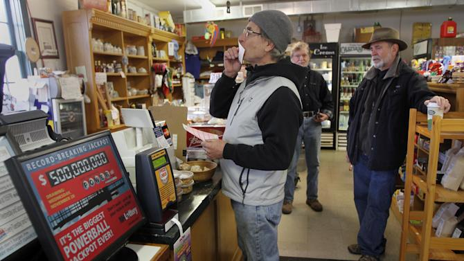 Retired Dr. Paul Kruzel kisses his lottery ticket for luck after buying it at the Canterbury Country Store Wednesday, Nov. 28, 2012 in Canterbury, N.H. (AP Photo/Jim Cole)
