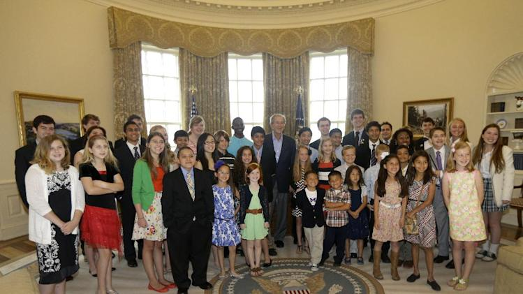 Former President George W. Bush, center, poses with 43 students from Dallas-Fort Worth Schools who were the first 43 official guest to tour the Bush Presidential Library on its' opening day,  Wednesday, May 1, 2013, in Dallas. (AP Photo/Tony Gutierrez)