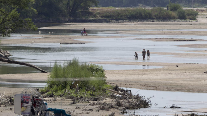 This photo from July 31, 2012 shows a beached air boat as bathers walk in the nearly dry Platte River near Yutan, Neb., Tuesday, July 31, 2012.  The latest U.S. Drought Monitor survey shows an increase in extreme drought conditions in four Plains states but a slight decrease in the overall area of the lower 48 states experiencing some form of drought. (AP Photo/Nati Harnik)