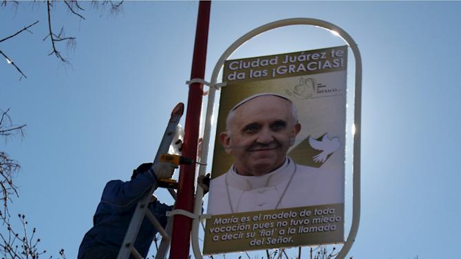 Workers put up a poster with an image of Pope Francis along a street at the border with the U.S. in Ciudad Juarez