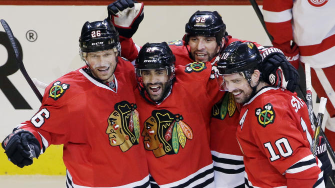 Chicago Blackhawks' Johnny Oduya (27), second from left, celebrates with Michal Handzus (26), Michal Rozsival (32), Patrick Sharp (10) and Patrick Kane (88) after scoring his goal during the third period of Game 1 of an NHL hockey playoffs Western Conference semifinal against the Detroit Red Wings in Chicago, Wednesday, May 15, 2013. (AP Photo/Nam Y. Huh)