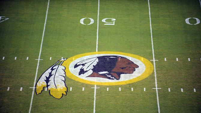 """FILE - In this Aug. 28, 2009, file photo, the Washington Redskins logo is displayed at midfield before the start of a preseason NFL football game in Landover, Md. The team's nickname, which some consider a derogatory term for Native Americans, has faced a barrage of criticism. But a new Associated Press-GfK poll shows that nationally, """"Redskins"""" still enjoys widespread support. (AP Photo/Nick Wass, File)"""