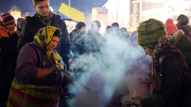 People prepare and serve soup at a camp set by opposition demonstrators on Independence Square in Kiev, on December 7, 2013