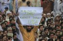A supporter of the Jamaat-ud-Dawa Islamic organization holds up a placard while taking part with others in an anti-American rally in Lahore