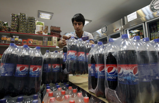 In this picture taken on Saturday, Sept. 8, 2012, Iranian worker Mahmoud Kouhi, adjusts family size bottles of Pepsi beverage, in a grocery store in northern Tehran, Iran. Even after decades of diplomatic estrangement and tightening economic sanctions, American products find their way to the Islamic Republic through back channel exporters, licensing workarounds and straightforward trade in goods not blocked by U.S. embargoes. In Iran, it's possible to check your email on an iPhone, sip a Coke and hit the gym wearing Nikes. (AP Photo/Vahid Salemi)