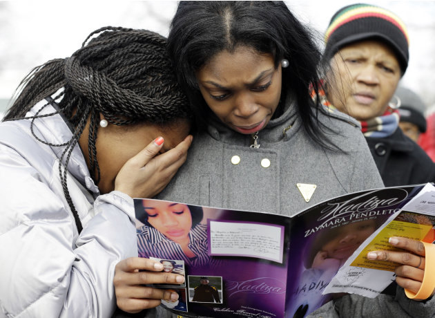 Danyia Bell, left 16, and Artureana Terrell , 16, react as they read a program for the funeral of Hadiya Pendleton outside the Greater Harvest Missionary Baptist Church after the funeral service of Ha