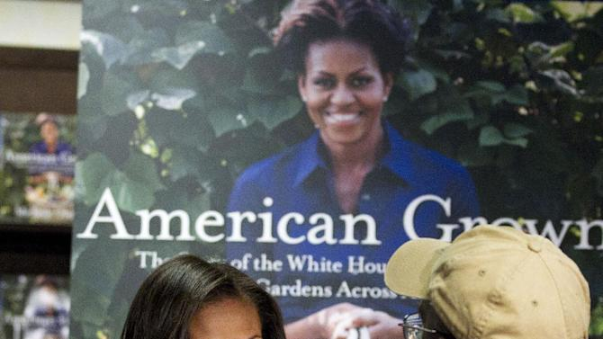 """First lady Michelle Obama signs copies of her book """"American Grown: The Story of the White House Kitchen Garden and Garden Across America,"""" in Washington, Tuesday, June 12, 2012.  (AP Photo/Jacquelyn Martin)"""