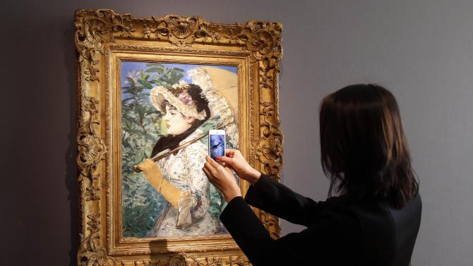 """A visitor takes a picture of the painting """"Le Printemps"""" by French painter Edouard Manet during its presentation at Christie's Auction House in Paris"""