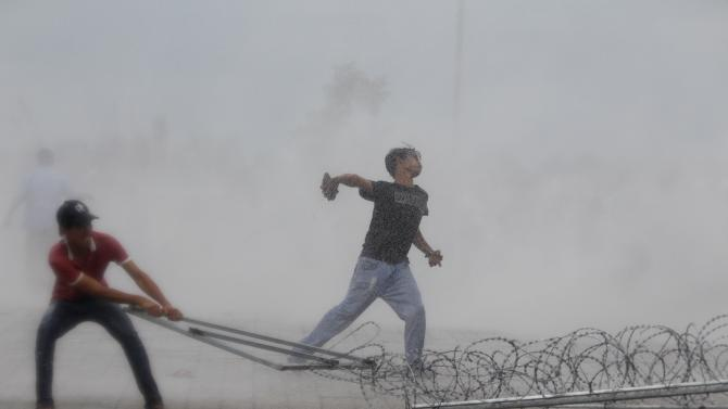 A protester supporting the opposition Cambodia National Rescue Party (CNRP) throws a stone as another tries to remove barbed wire barricades during clashes with police near the Royal Palace in central Phnom Penh