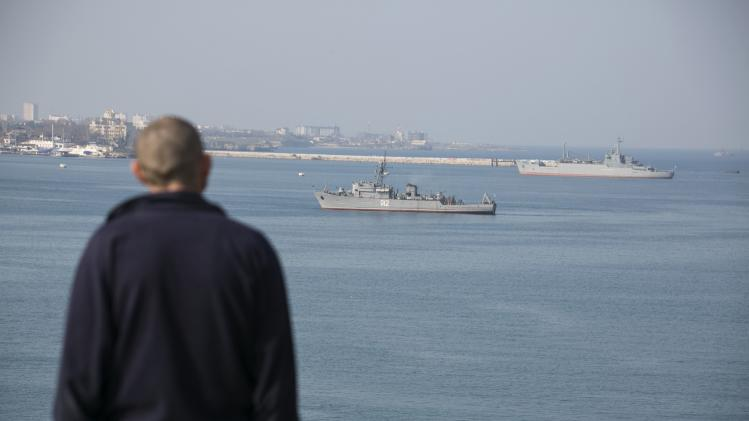 A man looks at Russian ships in Sevastopol, Crimea