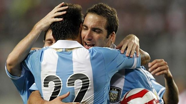 Agentina's Gonzalo Higuain (R) is embraced by team-ates Ezequiel Lavezzi (22) and Lionel Messi after he scored a goal against Peru during their 2014 World Cup qualifier (Reuters)