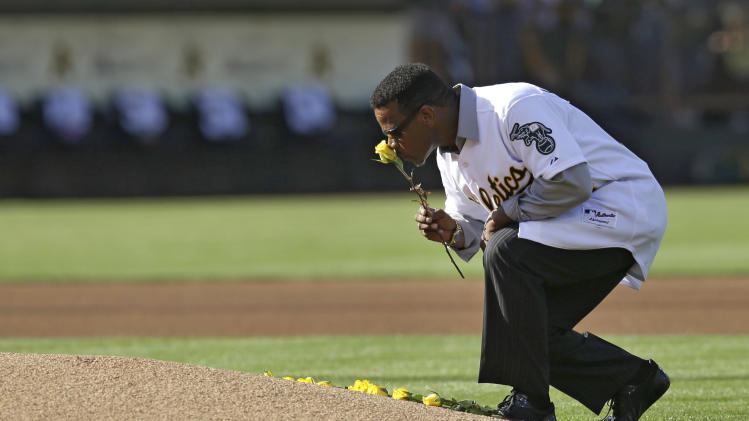 Former Oakland Athletic and Hall of Famer Rickey Henderson kisses a rose before laying it on the pitchers mound during a pre-game ceremony honoring the reunion of players from the 1989 world championship team prior to the baseball game against the Baltimore Orioles Saturday, July 19, 2014, in Oakland, Calif. (AP Photo/Ben Margot)