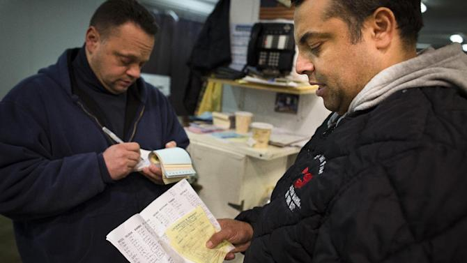 Roberto Nunez, a buyer for multiple high-end New York establishments, including Eataly Gourmet Food Market, places an order at the Fulton Fish Market, Friday, March 29, 2013, in New York. The Fulton Fish Market, located in the Hunts Point neighborhood of the Bronx, is the world's largest after Tokyo. In this football-field size refrigerated building, time and money is measured in thousand-dollar pieces of salmon whose price-for-quality is negotiated on the spot. The product goes to the buyer instantly and is trucked to restaurants or retail vendors. (AP Photo/John Minchillo)