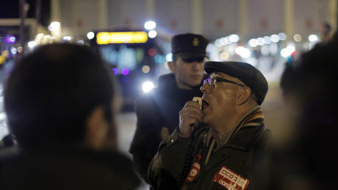 Protestors shout slogans to stop the buses to run as the police stand guard outside a main bus garage during a general strike in Madrid, Spain, Wednesday, Nov. 14, 2012. Spain's main trade unions stage a general strike, coinciding with similar work stoppages in Portugal and Greece, to protest government-imposed austerity measures and labor reforms. The strike is the second in Spain this year. (AP Photo/Andres Kudacki)