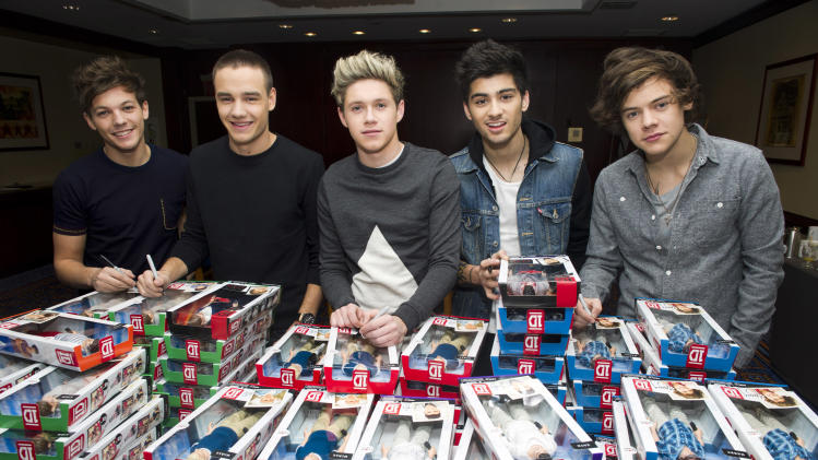 IMAGE DISTRIBUTED FOR HASBRO -Members of worldwide musical sensation One Direction, from left, Louis Tomlinson, Liam Payne, Niall Horan, Zayn Malik and Harry Styles sign boxes of their Hasbro dolls at a press event on Monday, Nov. 26, 2012, in New York. (Photo by Charles Sykes/Invision for Hasbro/AP Images)