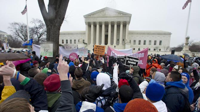 "FILE - In this Jan. 23, 2012 file photo, anti-abortion and abortion rights supporters stand face to face in front of the Supreme Court in Washington, Monday, Jan. 23, 2012, during the annual March For Life rally. There's been a lot of heated talk this year by Democrats contending that Republicans are waging a ""war on women."" That's hyperbole, retorts the GOP, but there are indeed stark differences between the two parties over these volatile issues. However, the next president _ Obama or Romney _ could have huge influence over the future of abortion policy if vacancies arise on the Supreme Court. For example, if two seats held by liberal justices were vacated and filled by Romney-nominated conservatives, prospects for a reversal of Roe v. Wade would increase. (AP Photo/Manuel Balce Ceneta, File)"