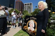 Suzie Kennedy (R), a Marilyn Monroe lookalike, stands beside a painting of Marilyn Monroe before a memorial service to mark the 50th anniversary at her death at Westwood Village Memorial Park Cemetery in Los Angeles on August 5