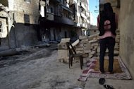 An opposition fighter prays in a street in Syria's northern city of Aleppo on September 11, 2013