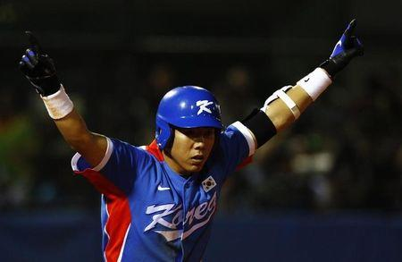South Korea's Kang Jung-ho raises his arms after hitting a home run against Taiwan in the ninth inning of their gold medal baseball game at the 16th Asian Games in Guangzhou
