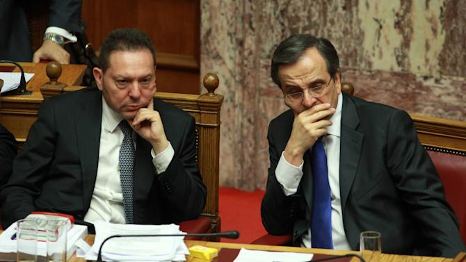 Greece's Prime Minister Antonis Samaras, right, and Finance Minister Yannis Stournaras attend a vote for the new austerity measures at the Greek parliament in Athens, Wednesday, Nov. 7, 2012. Greek lawmakers have narrowly passed a crucial austerity bill by majority vote, but with heavy dissent from within the three-party governing coalition. (AP Photo/Thanassis Stavrakis)