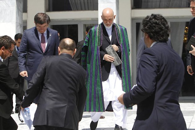 Afghan President Hamid Karzai, center, arrives for a group photo with the foreign attendees of the Asia Ministerial Conference at the foreign ministry in Kabul, Afghanistan, Thursday, June 14, 2012. Afghanistan&#39;s neighbors and regional heavyweights met in Kabul on Thursday to do something they rarely do _ try to tackle common threats and problems together.(AP Photo/Musadeq Sadeq)