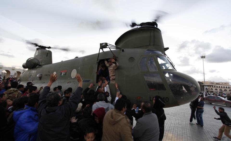 Libyans gather around a military helicopter, to shake the soldiers hands, at Nasr Square, during the second anniversary of the uprising that toppled longtime dictator Moammar Gadhafi in Benghazi, Libya, Sunday, Feb, 17, 2013.  (AP Photo/Mohammad Hannon)