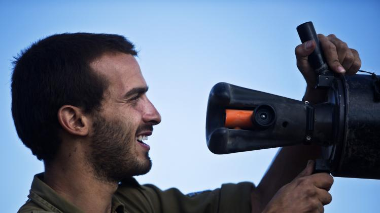 An Israeli soldier checks the barrel of a tank outside northern Gaza