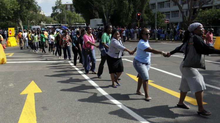 People hold hands in solidarity as they queue to view the body of former South African President Nelson Mandela outside the Union Buildings in Pretoria