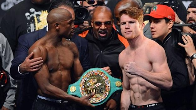 CEO of Mayweather Promotions Leonard Ellerbe (C) looks on as boxer Floyd Mayweather Jr. (L) tries to get boxer Canelo Alvarez (R) to hold a WBC belt (AFP)