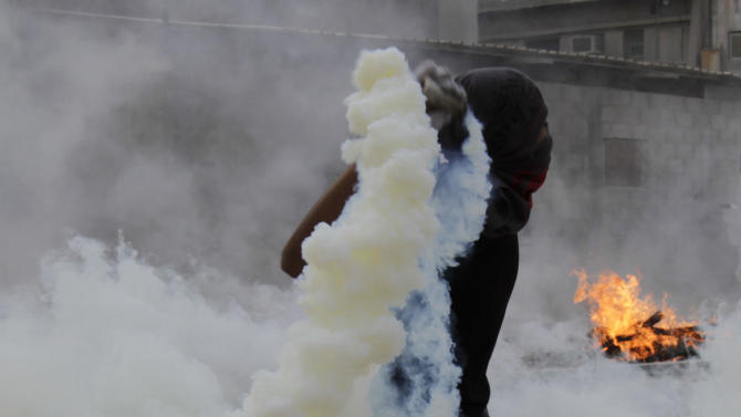 A Bahraini anti-government protester throws a tear gas canister fired by riot police back toward them Saturday, March 31, 2012, in Salmabad, Bahrain, on the outskirts of the capital of Manama. Bahraini security forces fired tear gas during clashes with protesters who gathered after authorities acknowledged that gunfire killed a young man early Saturday in anti-government demonstrations in the Gulf kingdom. (AP Photo/Hasan Jamali)